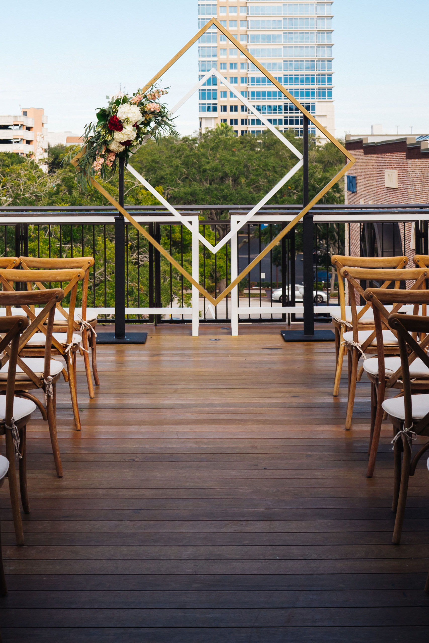 St. Petersburg Florida Wedding   St. Pete Venue Red Mesa Events   Rooftop Geometric Gold Ceremony Arch Backdrop   Wood Cross Back French Country Chairs