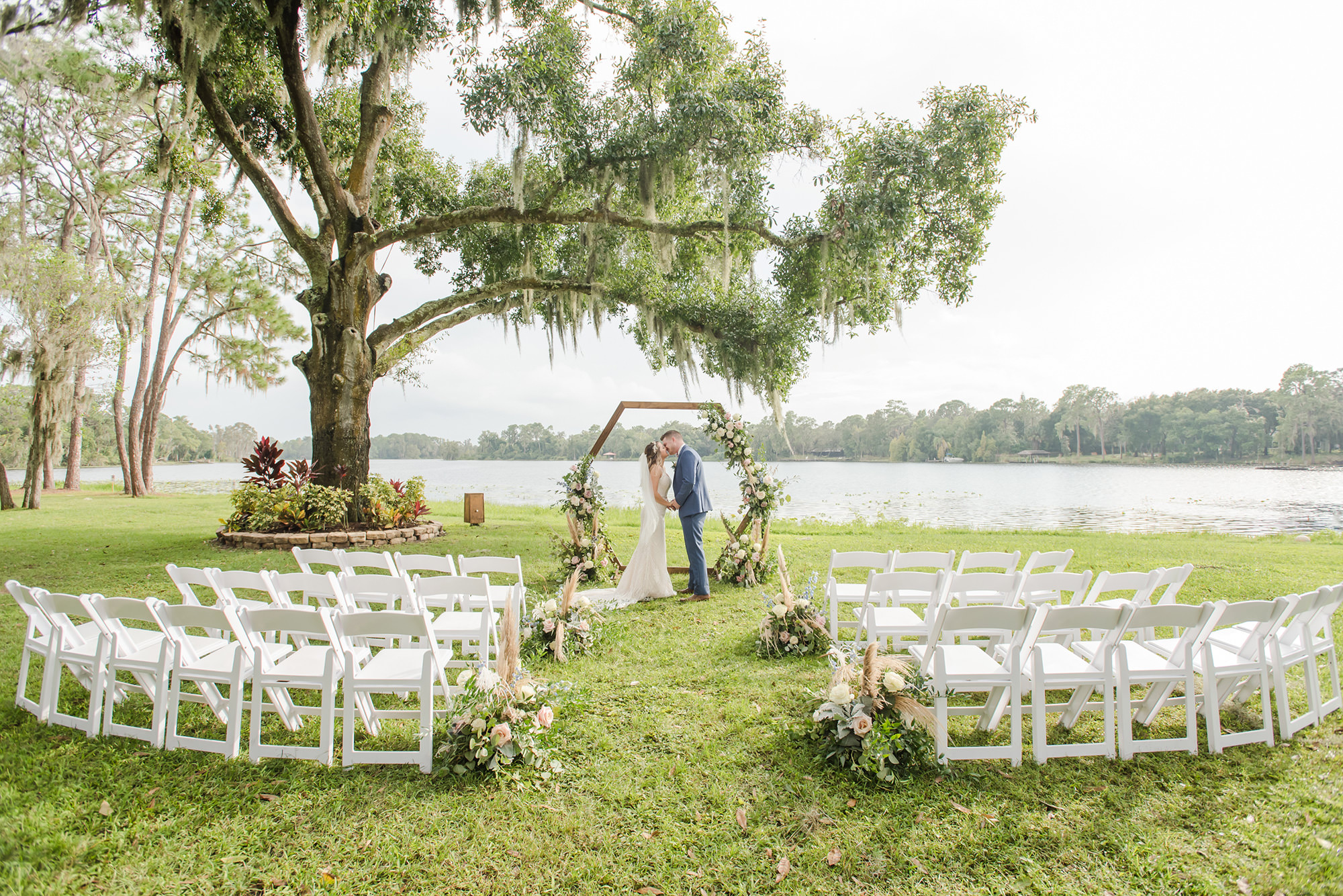 Florida Bride and Groom Kiss During Outdoor Waterfront Wedding Ceremony, Under Large Flowing Oak Tree, Rustic Wooden Hexagon Wedding Arch with Whimsical Inspired White and Dusty Rose and Pompous Grass Ceremony Flowers, White Chairs for Intimate Lakefront Ceremony   Tampa Bay Wedding Planner and Day of Coordinator Elegant Affairs by Design   Venue Barn at Crescent Lake