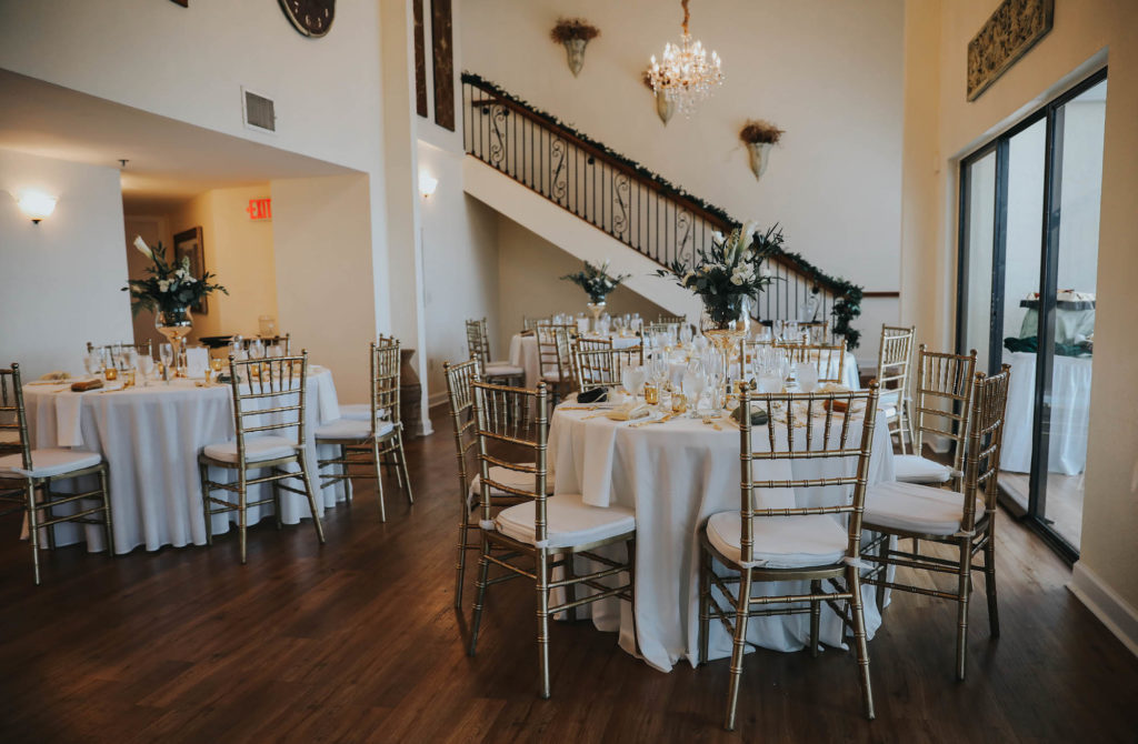 Elegant, Garden Inspired Wedding Decor and Reception, Round Tables with White Linens, Gold Chiavari Chairs, Tall Floral Centerpieces with Green Palms, White Flowers, and Gold Candle Votives, in Clearwater Modern Ballroom with dark wood floors, tall vaulted ceilings, and iron rod staircase | Tampa Bay Wedding Florist Brides N Blooms | Florida Wedding Venue Beso Del Sol | Tampa Wedding Decor Rentals Outside the Box Event Rentals