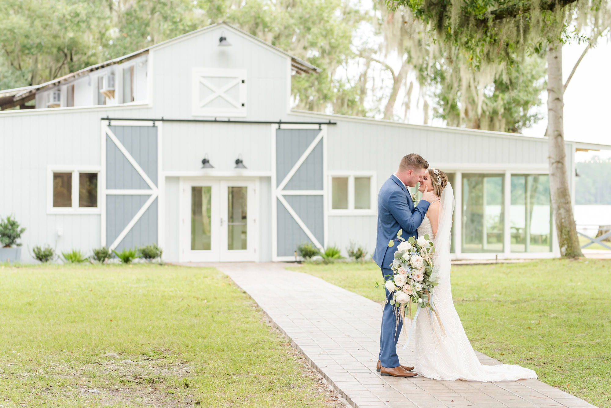 Tampa Bay Bride and Groom Intimate Embrace outside Barn at Crescent Lake, Groom in Dark Blue Suite, Bride holding Bouquet Whimsical Dusty Rose Florals, Ivory Roses, Light Blue Flowers, Pompous Grass, with Eucalyptus Leaves Greenery