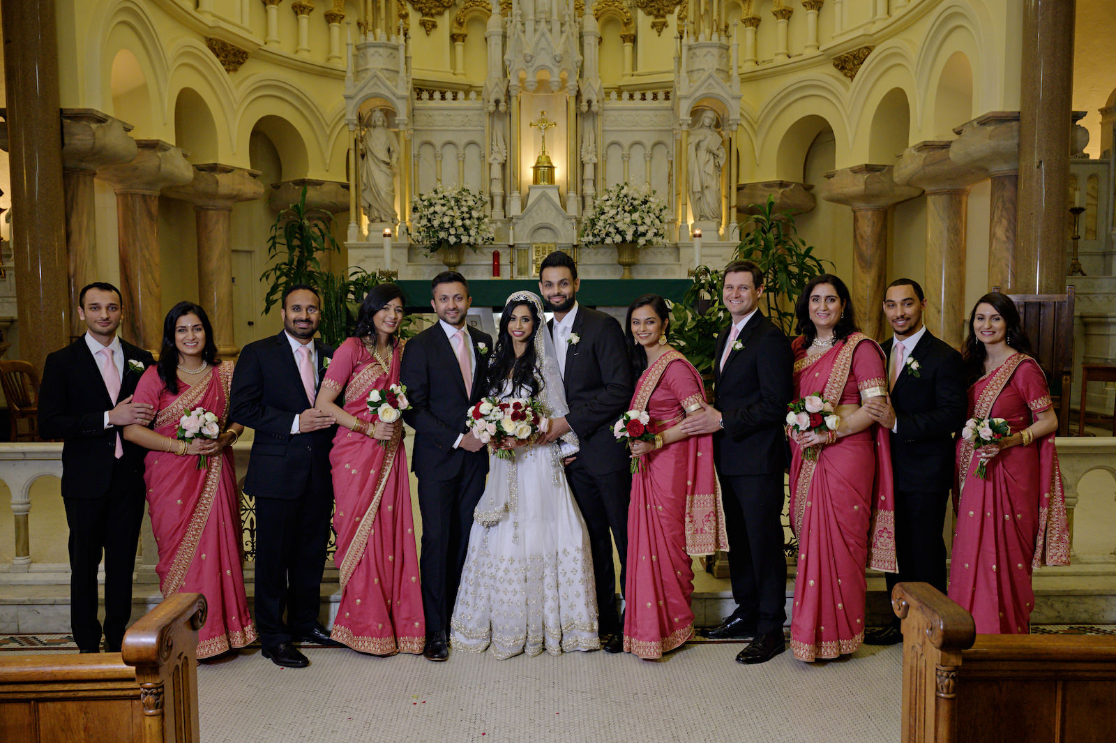 Florida Multicultural Indian Catholic Wedding Party Portrait with Berry Pink Fuchsia Sari and Black Suit Tux Wedding Portrait | Catholic Wedding Ceremony at Sacred Heart Catholic Church | Tampa Bay Wedding Hair and Makeup Artist Michele Renee the Studio