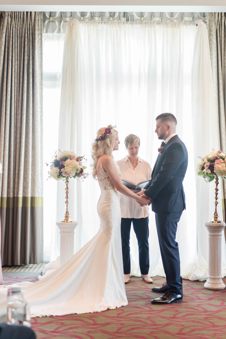 Bride and Groom Exchanging Vows | St. Pete Wedding Venue The Birchwood | Indoor Ballroom Wedding Ceremony with Floral Candlestick and Pipe and Drape Backdrop | Stella York Lace Sheath Spaghetti Strap Empire Waist Wedding Dress Bridal Gown | Groom Classic Black Suit Tux