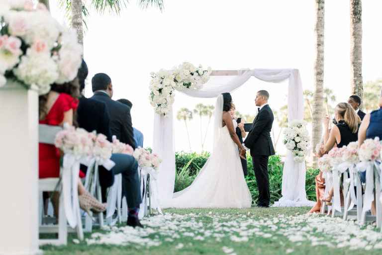 Classic Elegant Wedding Ceremony Garden Waterfront Wedding Decor, Rectangular Arch with White Draping and Floral Arrangements, Bride and Groom Exchanging Vows Ceremony Portrait   Hotel Wedding Venue Ritz Carlton Sarasota   Tampa Wedding Planner Special Moments Event Planning   Officiant A Wedding with Grace