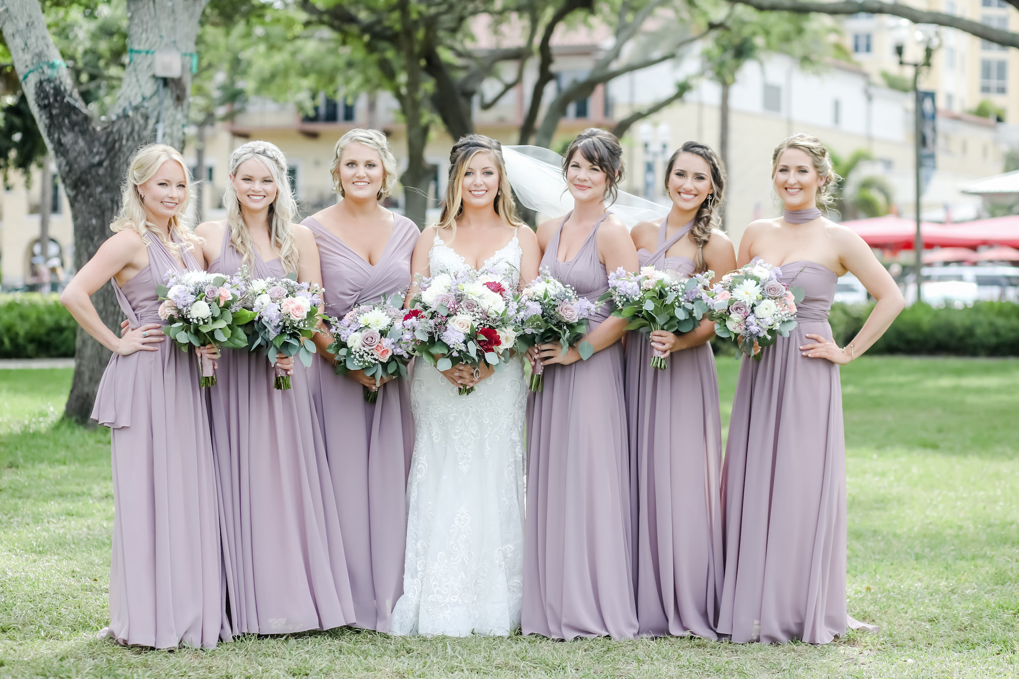 Florida Bride and Bridesmaids in Straub Park, Wearing Long Mix and Match Mauve Light Purple Dresses, Bride Holding Floral Bouquet with Red, White, Pink Roses Flowers with Greenery   Tampa Bay Hair and Makeup Artist Michele Renee The Studio   Florida Wedding Photographer Lifelong Photography Studio   Planner Blue Skies Weddings and Events