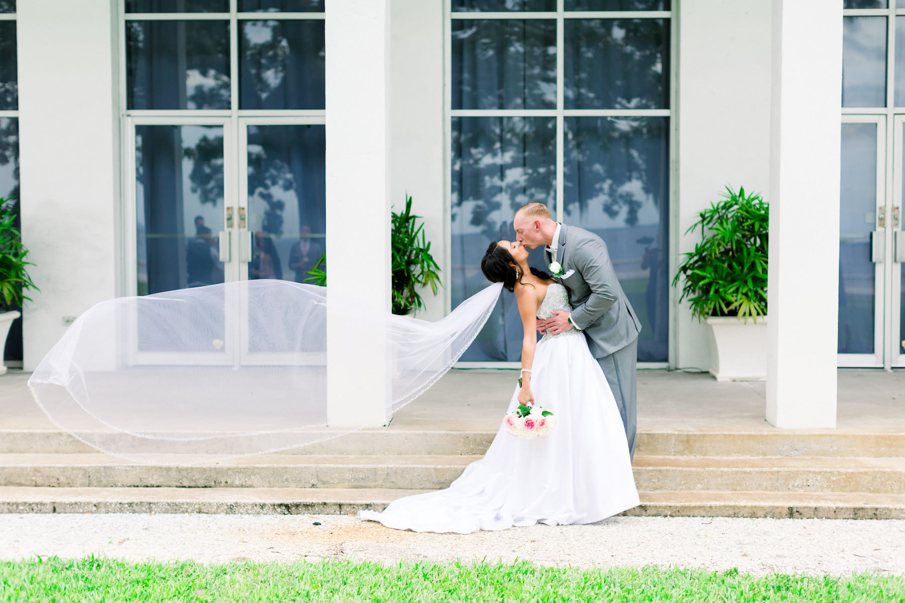 Romantic Creative Bride and Groom with Veil Blowing in the Wind First Look Wedding Portrait | Wedding Photographer Shauna and Jordon Photography | Wedding Venue Tampa Garden Club | Wedding Dress Truly Forever Bridal