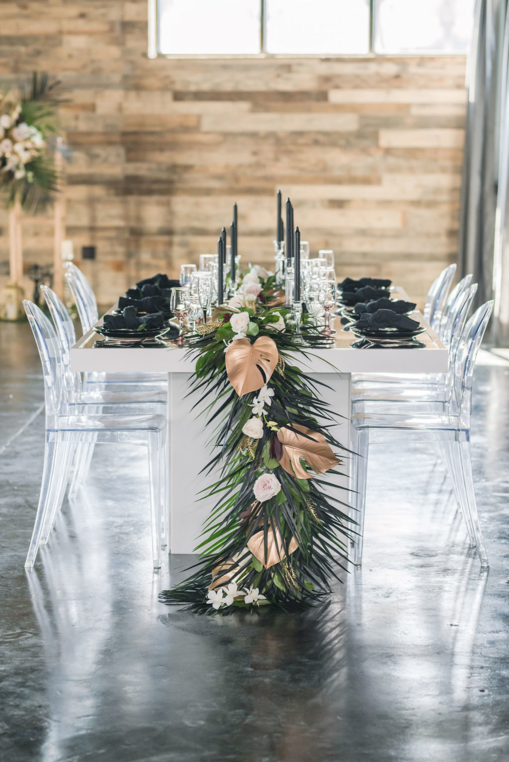 Dark Luxe, Romantic Wedding Styled Shoot Decor, Long White Table with Palm Fronds, Gold Painted Monstera Leaves, Blush Pink Table Runner, Black Candlesticks, Ghost Acrylic Chairs | Tampa Bay Wedding Planner Elegant Affairs by Design | Madeira Beach Wedding Venue The West Events Space