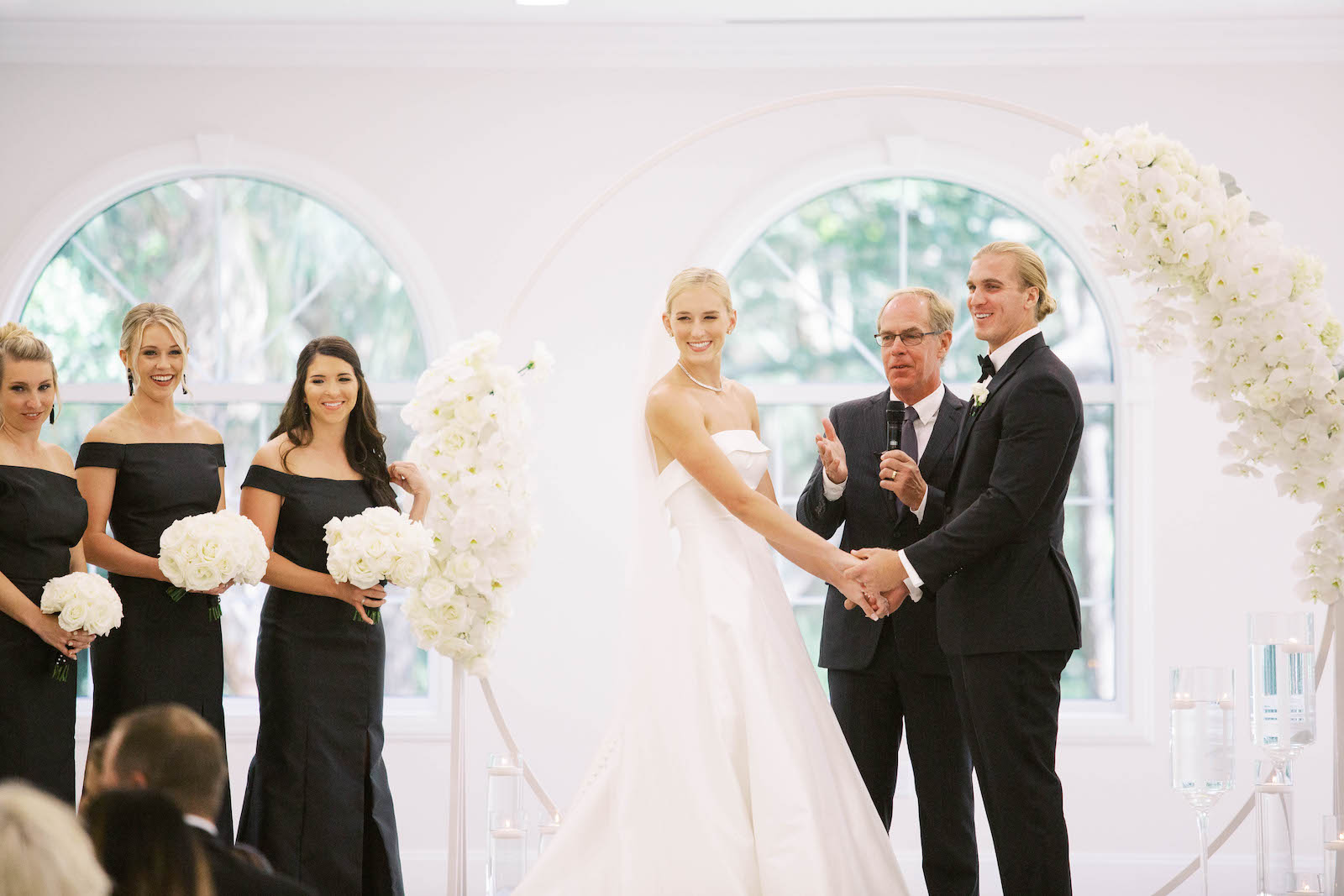 Classic Traditional Bride and Groom Exchanging Wedding Ceremony Vows, Circular Arch with White Orchid Arrangements, Bridesmaids in Black Off the Shoulder Matching Dresses Holding White Floral Bouquets | Tampa Bay Wedding Planner Parties A'la Carte | Safety Harbor Church Wedding Venue Harborside Chapel