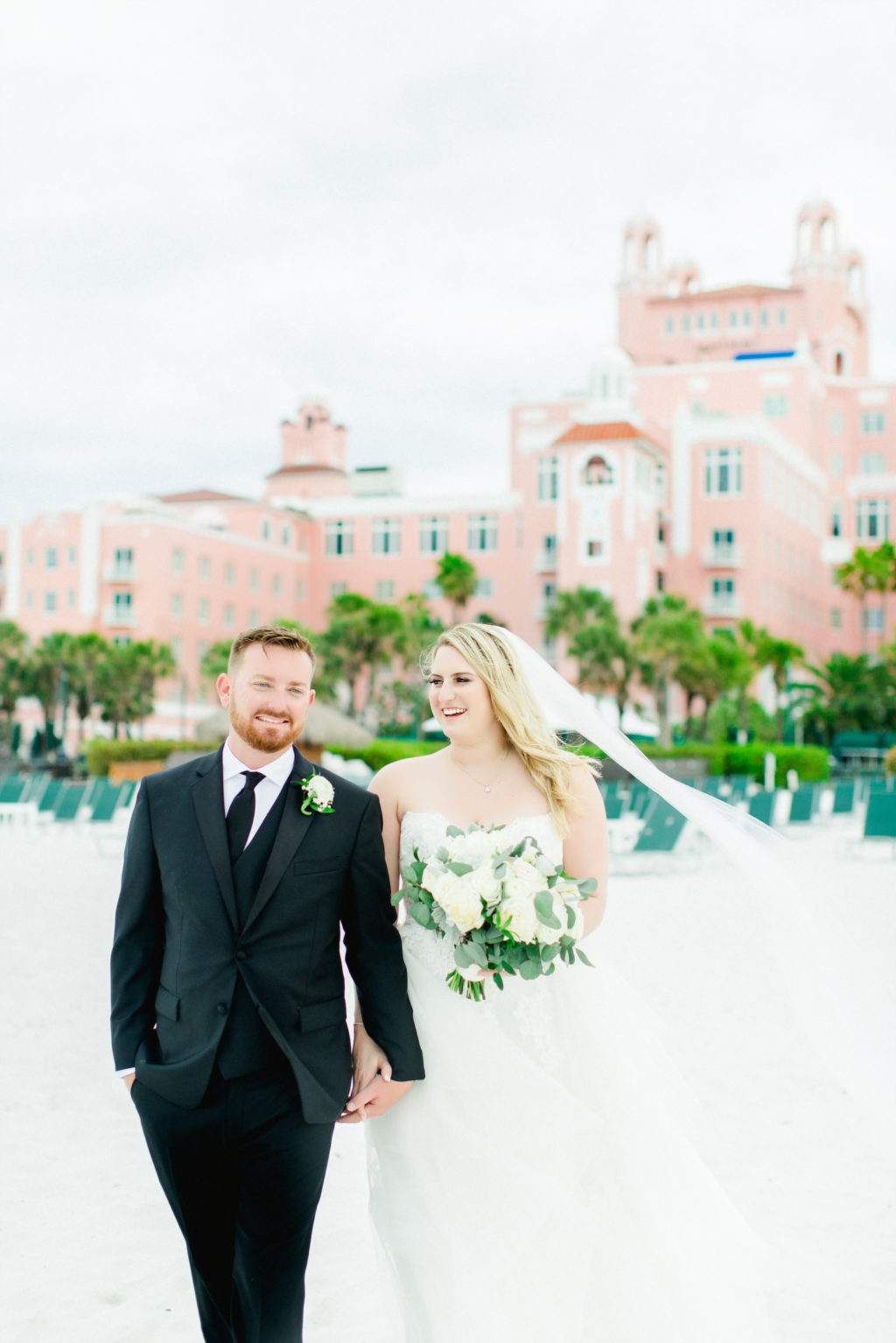 Lace Wedding Dress Bridal Gown with Long Cathedral Veil | Bride and Groom Outdoor Hotel Beach Portraits | St Pete Beach Wedding Venue The Don Cesar | Classic Greenery White Flowers Bouquet | Groom Wearing Classic Black Suit Tux | Pink Palace