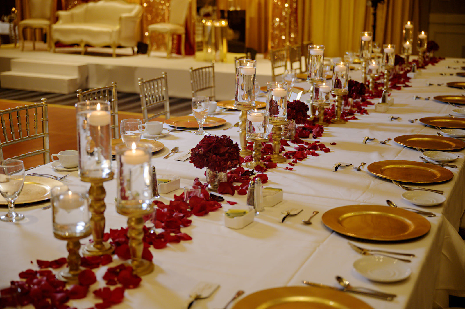 Elegant Florida Multicultural Indian Catholic Wedding Reception Feasting Table with Red Rose Petals and Gold Candle Centerpieces with Gold Chiavari Chairs and Gold Charger Plates