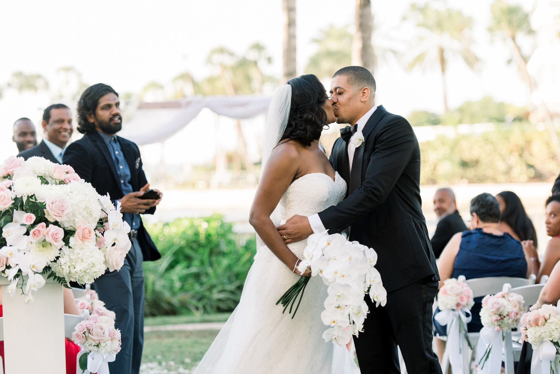 Intimate Classic Bride and Groom Kissing Wedding Ceremony Recessional Portrait | Tampa Wedding Planner Special Moments Event Planning | Garden Waterfront Hotel Wedding Venue Ritz Carlton Sarasota