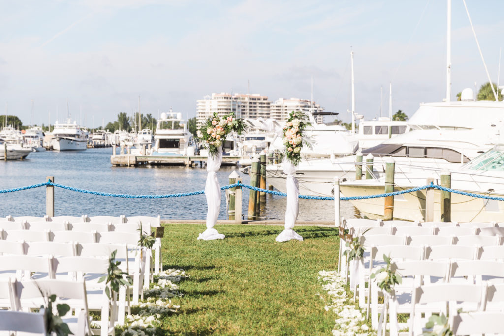 Peach, Pink, and White Wedding Ceremony Arch Decor with Greenery and Draping | Tropical Waterfront Florida Lawn Wedding Ceremony | Sarasota Wedding Venue The Resort at Longboat Key Club Marina