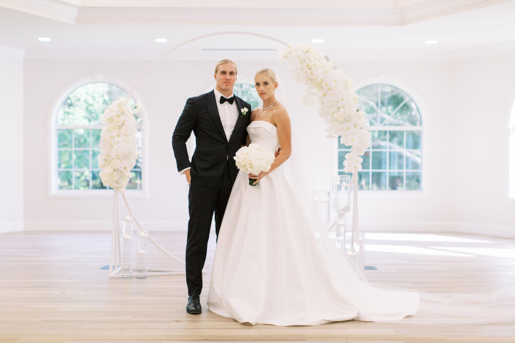 Classic Traditional Bride in Strapless Crepe Romona Keveza Ballgown Wedding Dress Holding White Floral Bouquet, Groom in Black Tuxedo Portrait in Front of Circular Arch with White Orchid Arrangements | Tampa Bay Wedding Planner Parties A'la Carte | Safety Harbor Church Wedding Venue Harborside Chapel