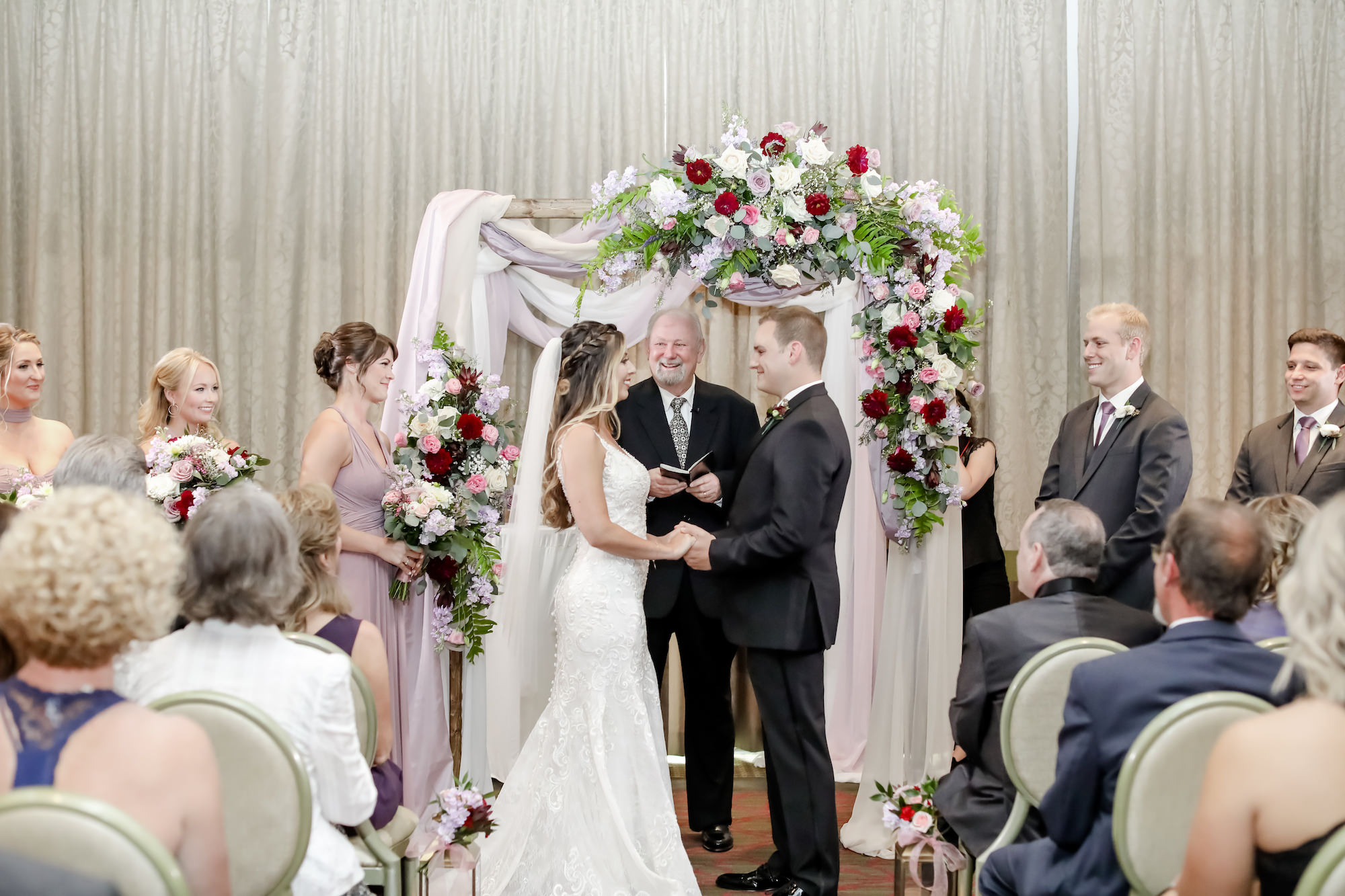 Tampa Bay Bride and Groom Exchange Vows in Ballroom Ceremony, Under Romantic Floral Wedding Arch with Red, White and Mauve Roses, Purple Flowers with Greenery, Ivory Draping   Downtown St. Pete Wedding Planner Blue Skies Weddings and Events   Florida Wedding Photographer Lifelong Photography Studio