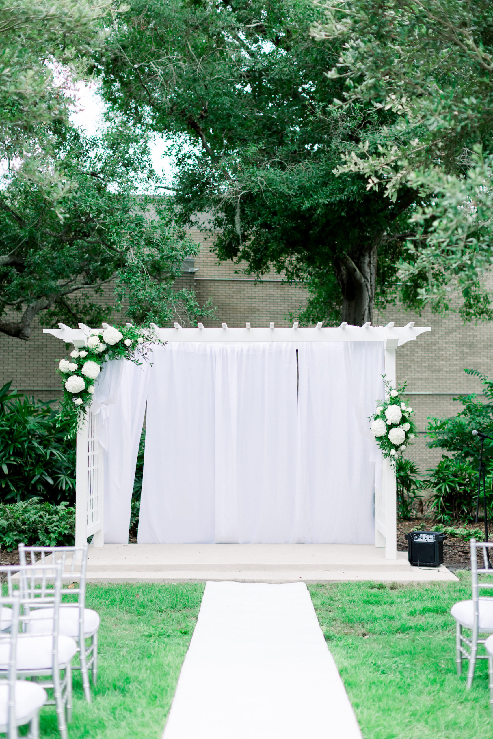 Wedding Ceremony Decor, Arbor Arch with White Draping and Floral Arrangements, White Aisle Runner, Silver Chiavari Chairs | Outdoor Wedding Venue Tampa Garden Club | Wedding Photographer Shauna and Jordon Photography