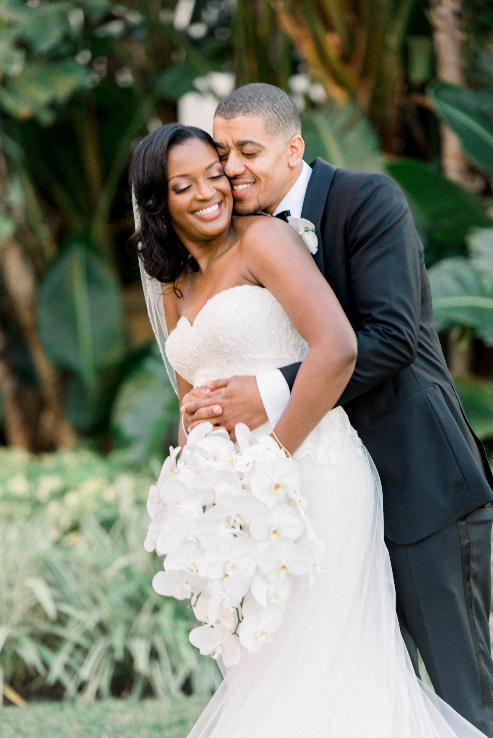 Classic Bride in Lace Strapless Sweetheart Wedding Dress Holding White Orchid Floral Bouquet, Groom in Black Tuxedo