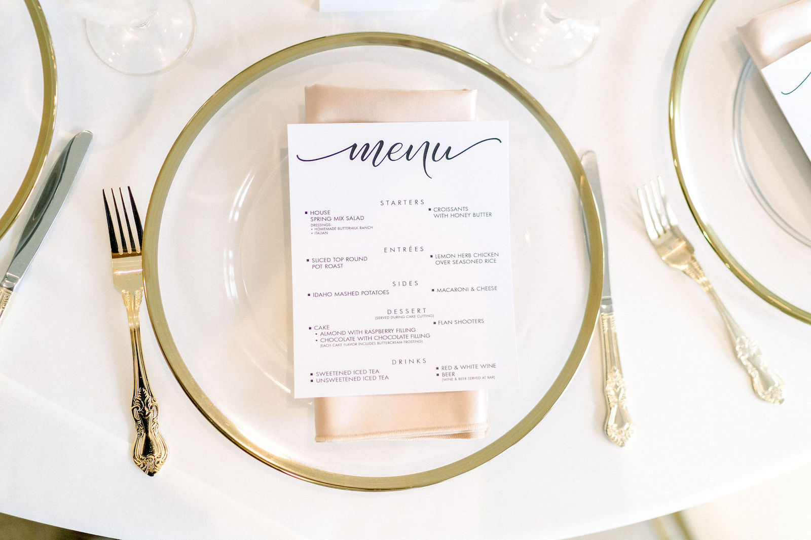 Wedding Reception Table Place Setting With Clear Glass Charger Plates With Gold Rim And Gold Flatware Silverware Classic Traditional Menu Card On Champagne Gold Satin Napkin Marry Me Tampa Bay