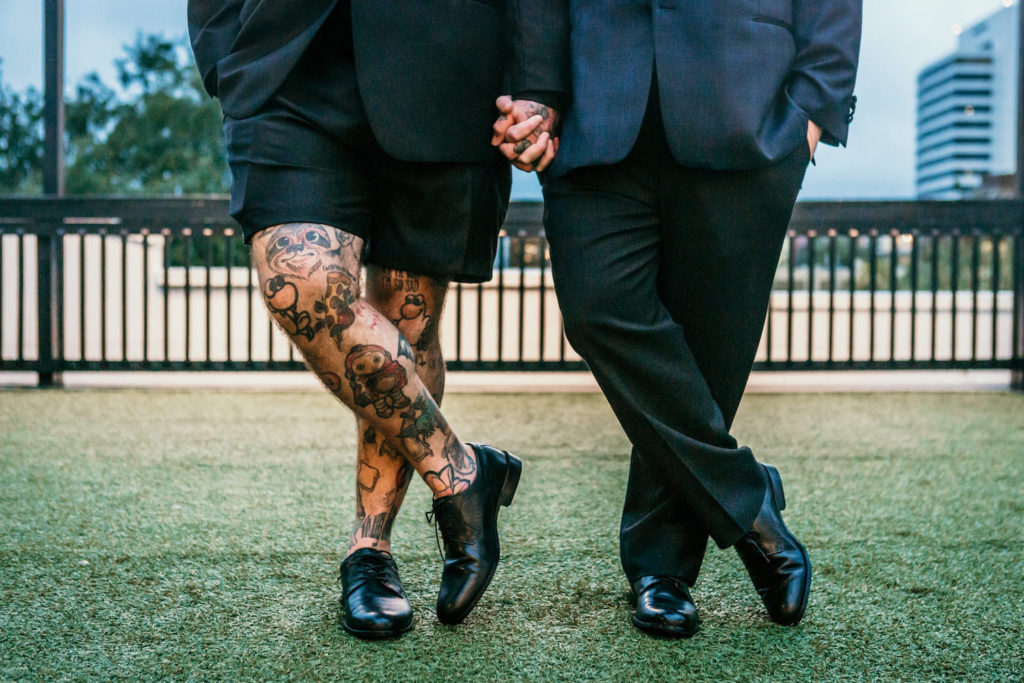 Creative Same Sex Gay Grooms Holding Hands, Groom in Dress Shorts and Leg Tattoos Wedding Portrait | St. Pete Unique Wedding Venue Station House