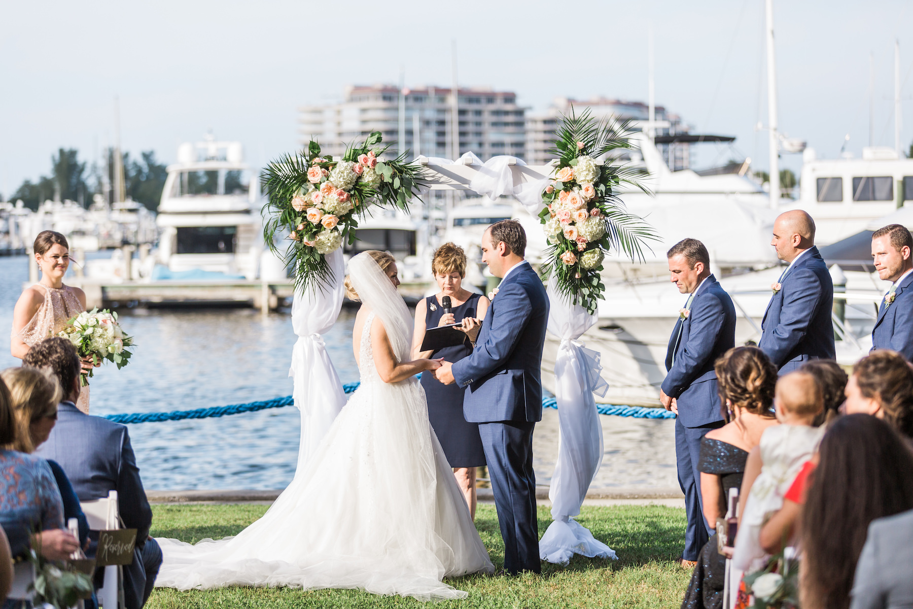 Peach, Pink, and White Wedding Ceremony Arch Decor with Greenery and Draping | Tropical Waterfront Florida Lawn Wedding Ceremony | Sarasota Wedding Venue The Resort at Longboat Key Club Marina | Sarasota Wedding Officiant A Wedding with Grace