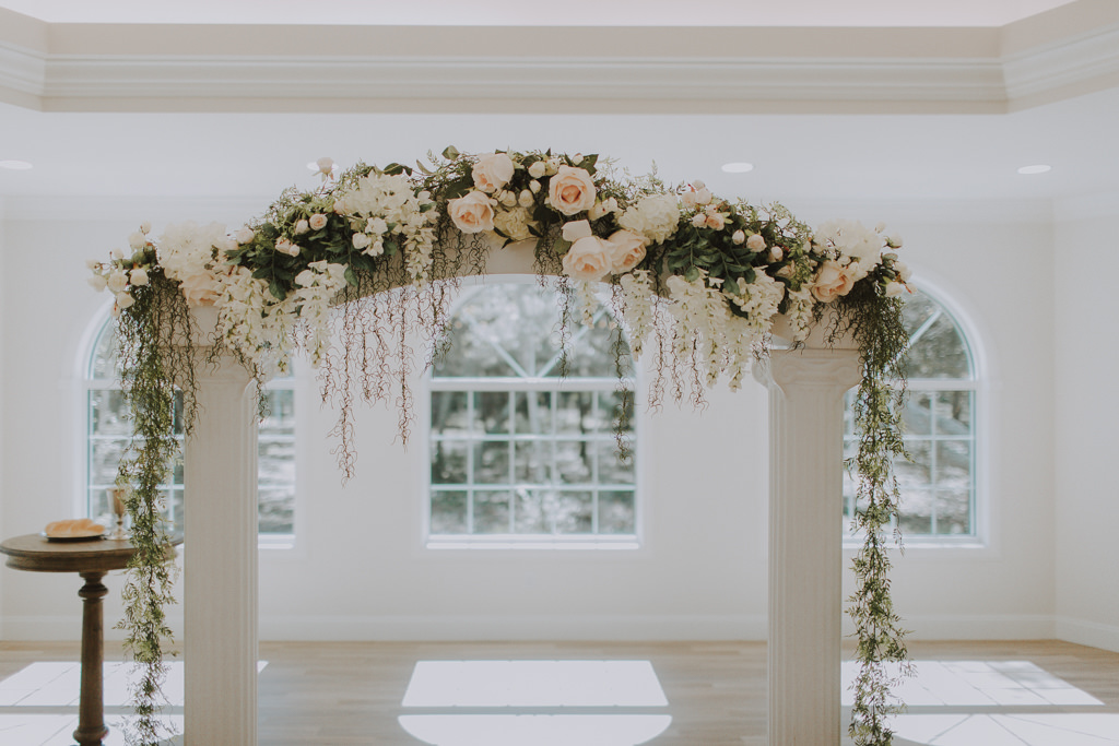 White Wedding Ceremony Column Pillar Arch Backdrop | Natural Loose Greenery Floral Arrangement with Blush Pink Champagne Roses and Greenery Garland with Hanging Moss