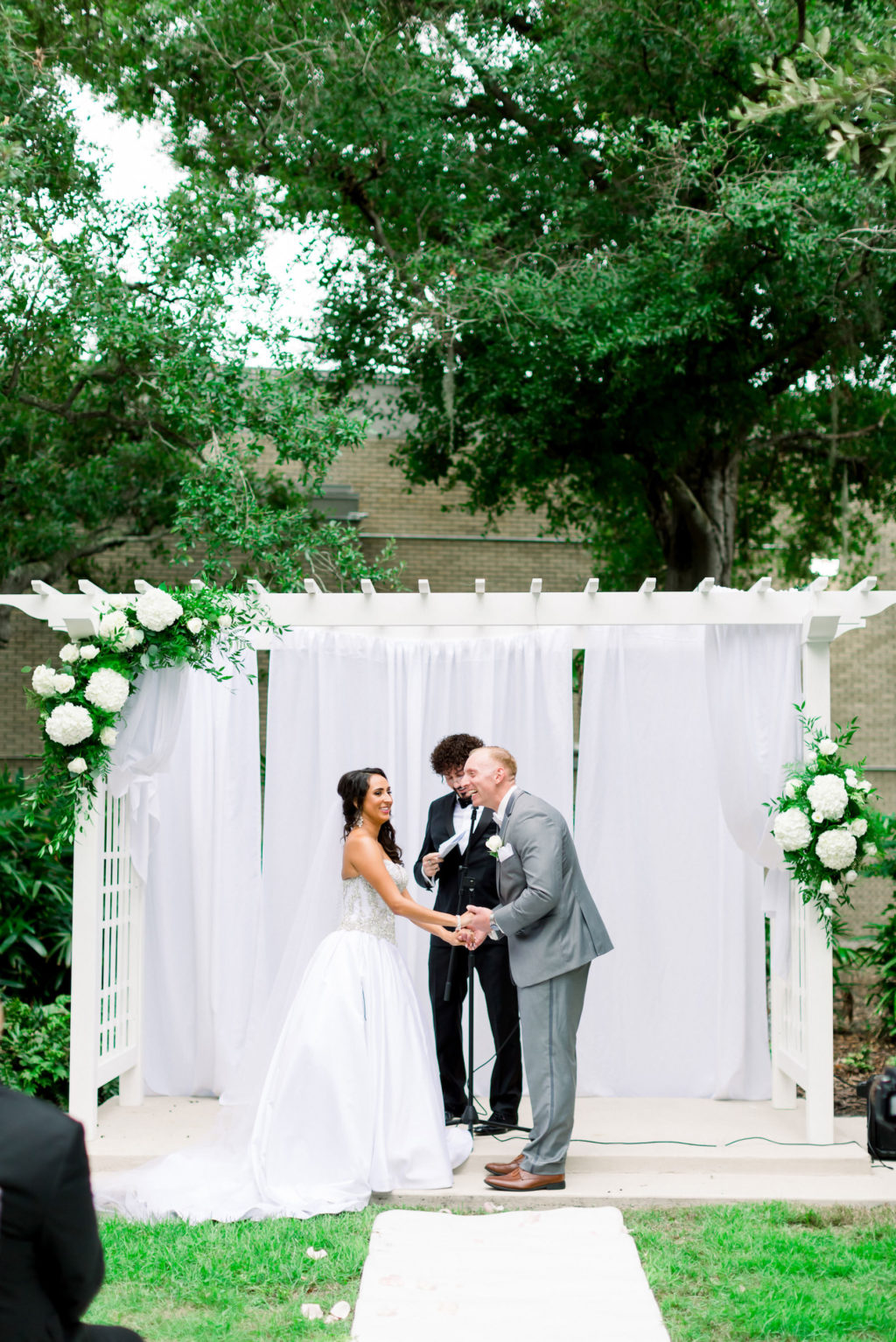 Romantic Bride and Groom Exchanging Vows Wedding Ceremony Portrait Under White Arbor Arch with Hydrangeas and Greenery Floral Arrangements and White Draping | Wedding Venue Tampa Garden Club | Wedding Photographer Shauna and Jordon Photography | Wedding Dress Truly Forever Bridal