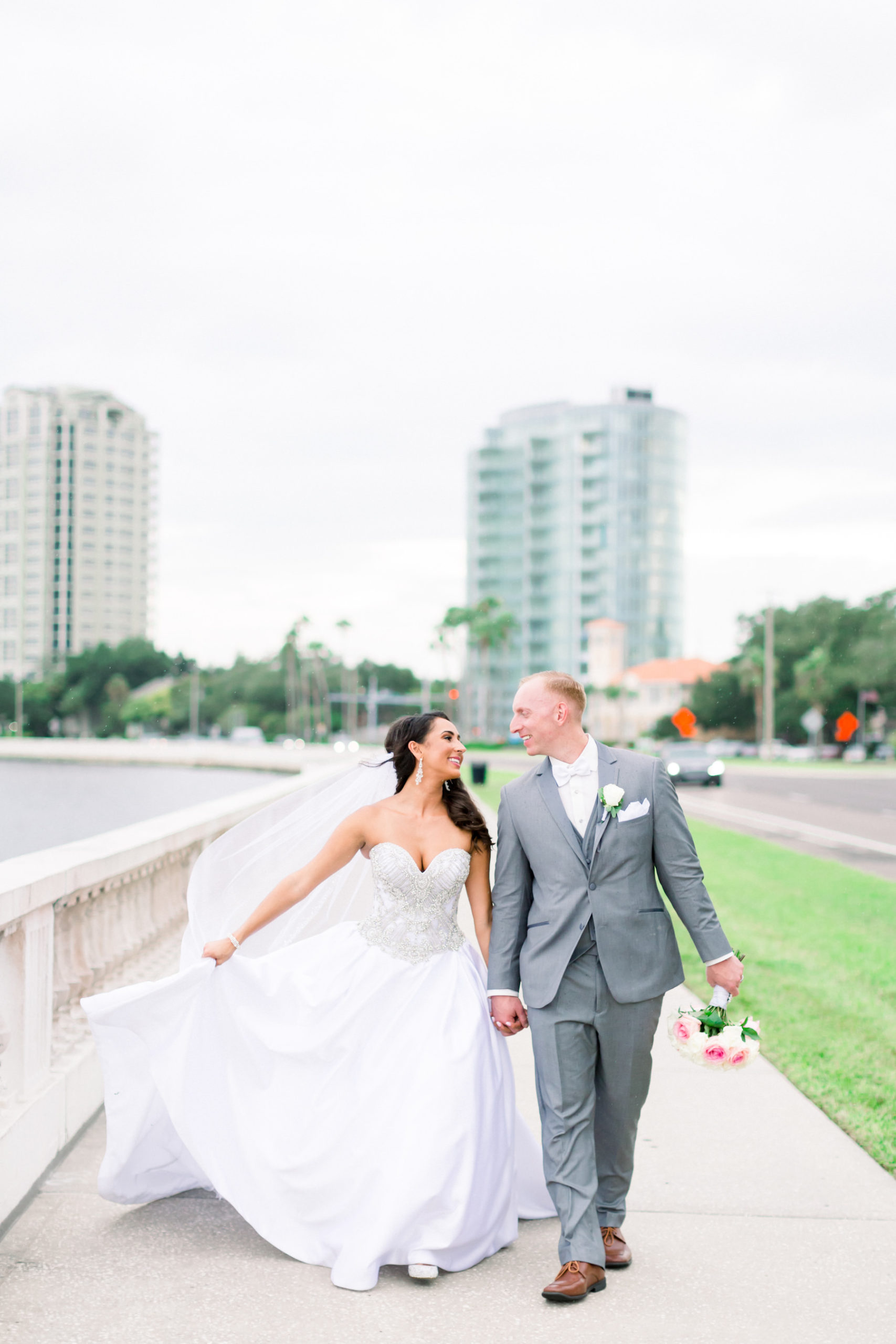 Bride in Strapless Sweetheart Rhinestone Bodice Ballgown Wedding Dress with Groom in Gray Suit Walking Down Bayshore Boulevard | Tampa Bay Wedding Photographer Shauna and Jordon Photography | Wedding Dress Truly Forever Bridal