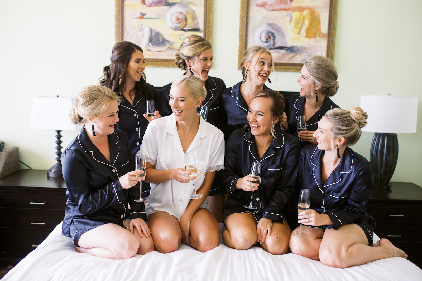 Tampa Bride and Bridesmaids in Matching Navy Blue Robes Drinking Champagne Getting Wedding Ready Hotel Bed Portrait
