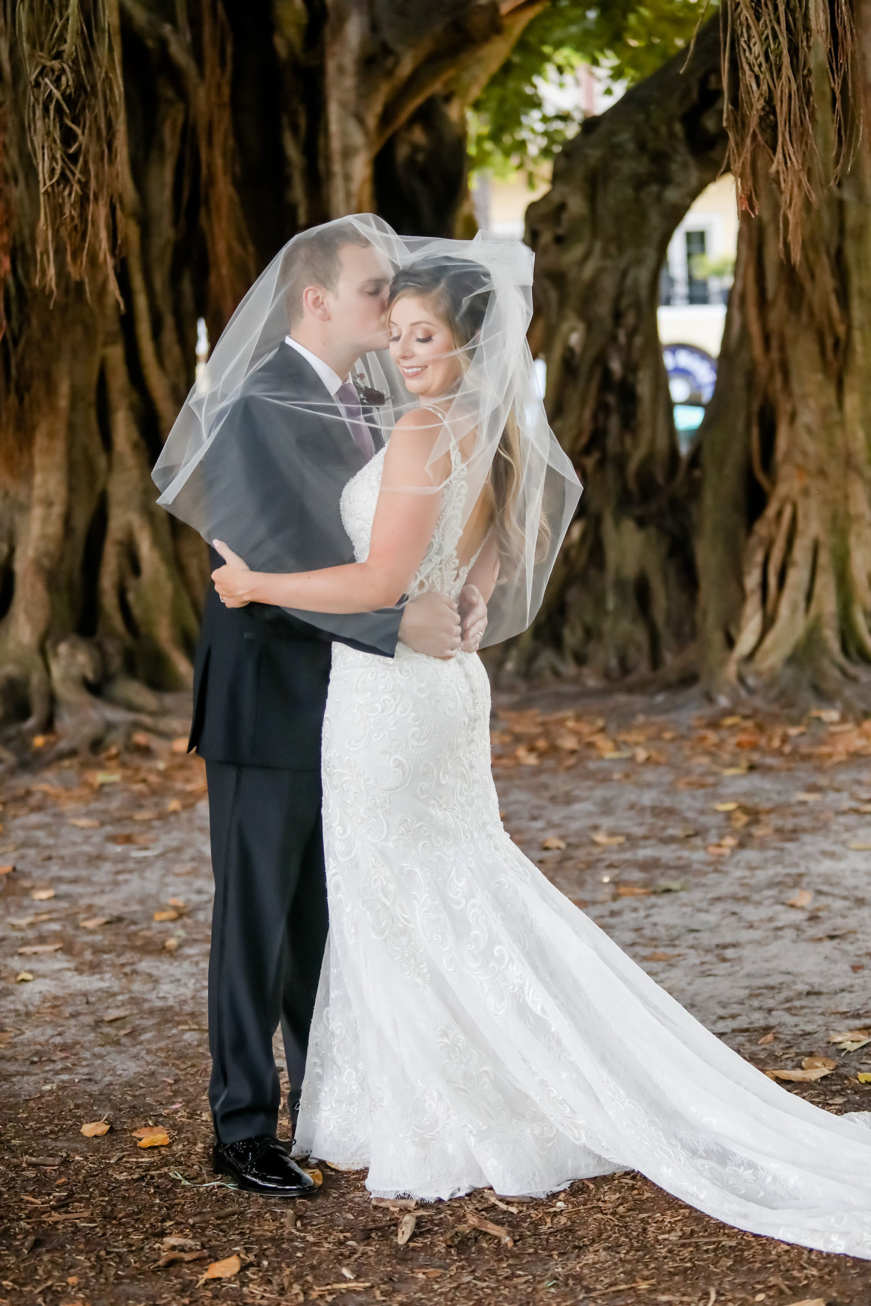 Creative Florida Bride and Groom Under Wedding Veil Embrace In Front of Banyan Trees in Straub Park Downtown St. Petersburg   Tampa Bay Hair and Makeup Artist Michele Renee The Studio   Florida Wedding Photographer Lifelong Photography Studio