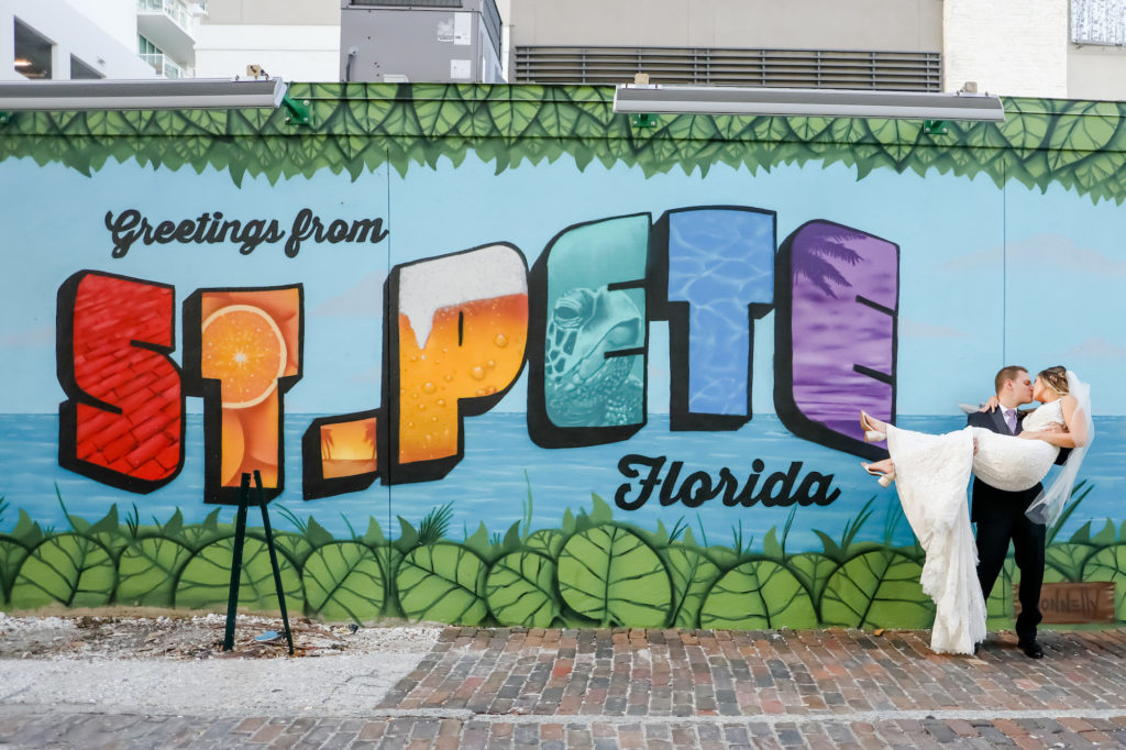 Florida Bride and Groom in front of Greetings from St. Pete Florida Wall Art Mural in Downtown St. Petersburg | Tampa Bay Wedding Photographer Lifelong Photography Studio