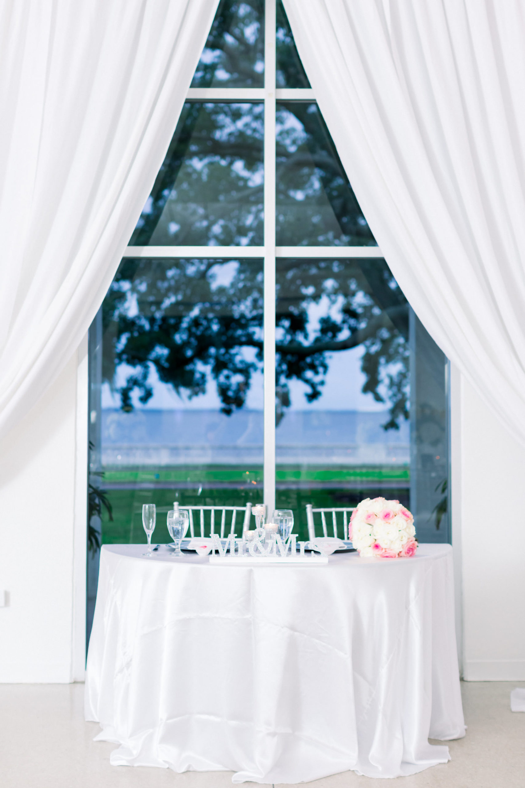 Garden-Glam Wedding Reception Decor, Waterfront View Sweetheart Table with White Linen, Pink and White Roses Floral Bouquet, White Draping | Wedding Venue Tampa Garden Club | Wedding Photographer Shauna and Jordon Photography