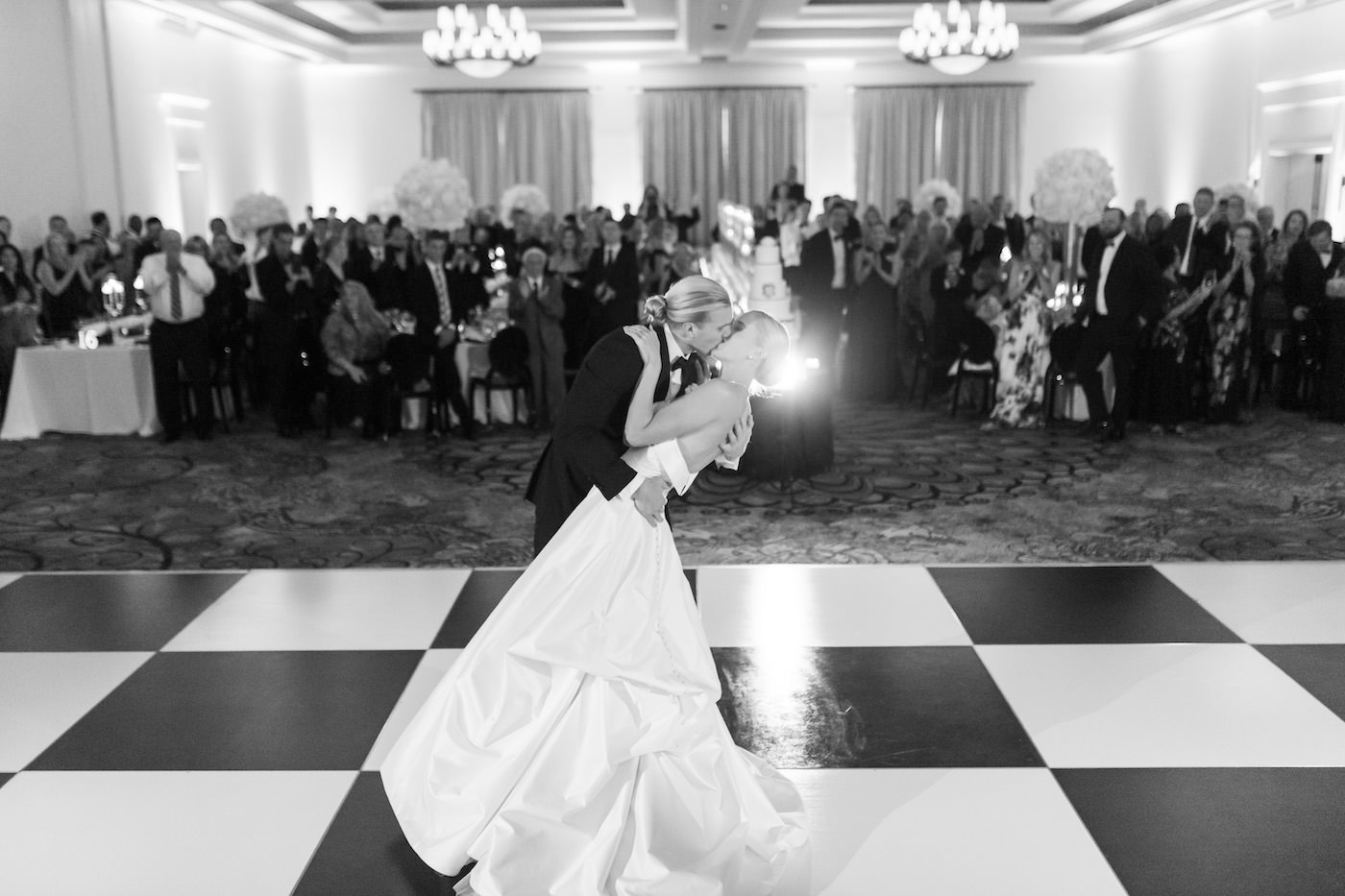 Classic Timeless Bride and Groom Black and White First Dance Dip Wedding Portrait on Black and White Checkered Dance Floor | Clearwater Beach Hotel Wedding Venue Sandpearl Resort