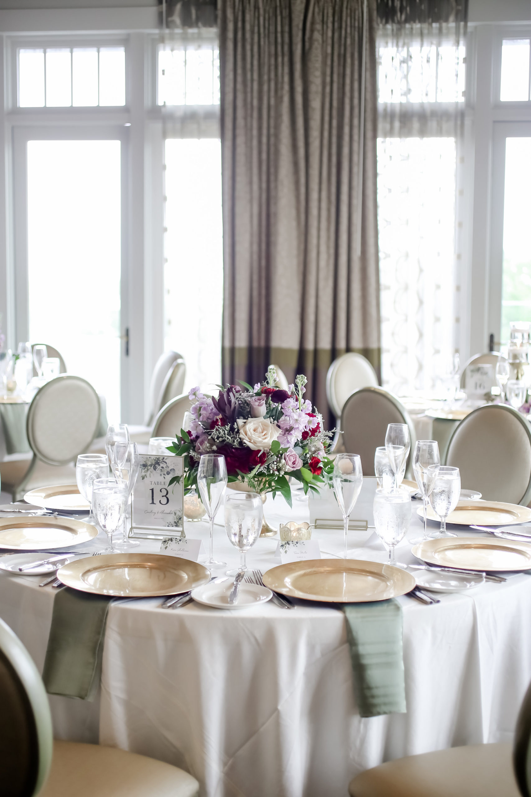 Elegant Spring Time Inspired Wedding Decor at Reception in Chic Ballroom with Natural Lighting, Round Tables with White and Green Linens, Low Floral Centerpieces with Mauve, Purple, Red, and Pink Flowers, Gold Chargers   Florida Downtown St. Pete Boutique Hotel The Birchwood   Tampa Bay Wedding Photographer Lifelong Photography Studio   Planner Blue Skies Weddings and Events