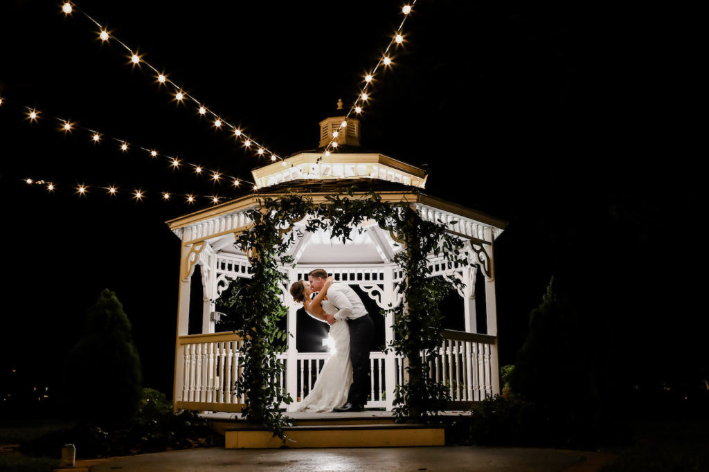 Romantic Intimate Bride and Groom NIghttime Wedding Portrait Under White Gazebo with Greenery Arch and String Lights | Wedding Photographer Lifelong Photography Studio | Tampa Wedding Planner Blue Skies Weddings and Events | Waterfront Wedding Venue Davis Islands Garden Club