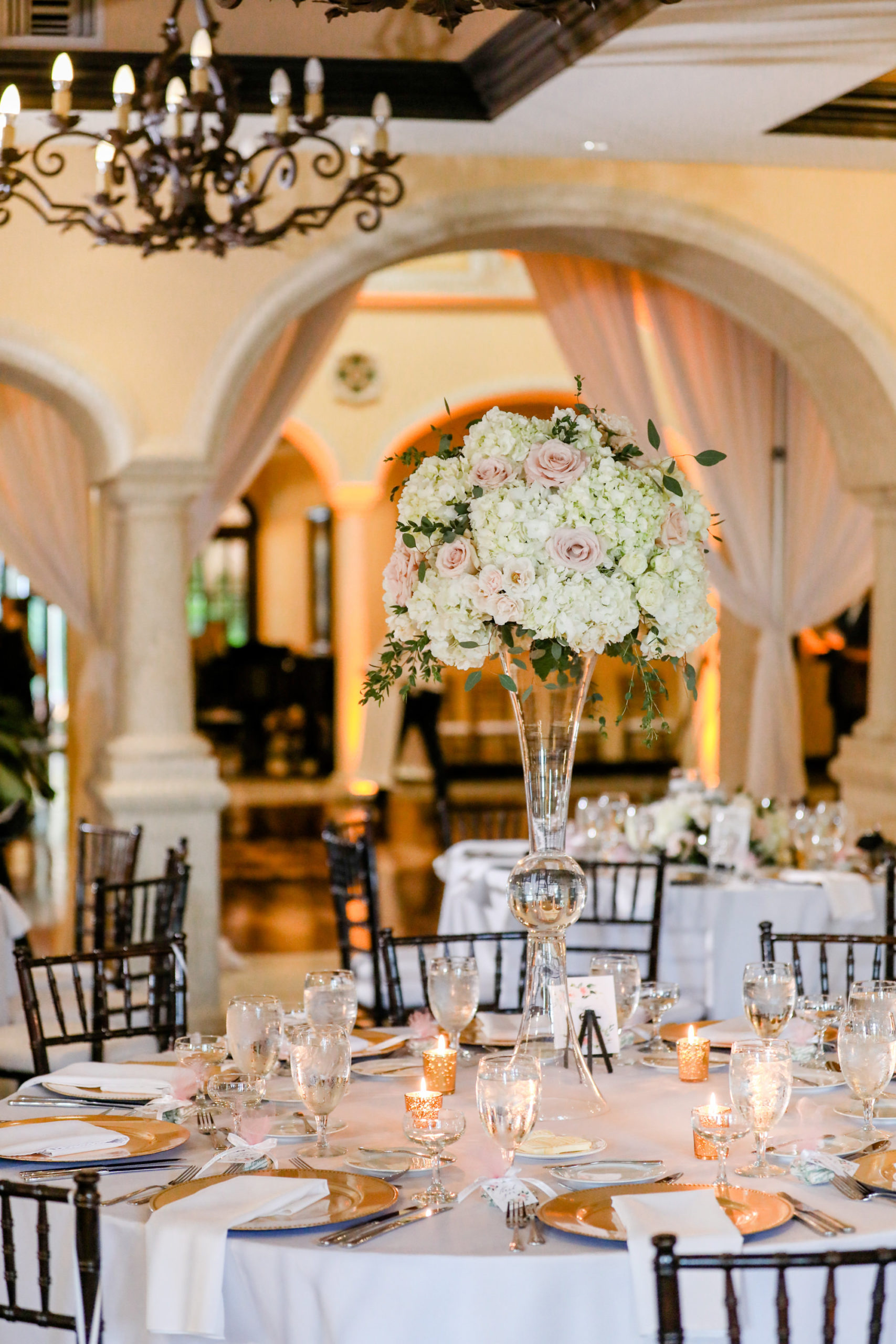 Tampa Wedding Venue Avila Golf & Country Club | Indoor Ballroom Reception with Chiavari Chairs and Chandeliers | White and Blush Dusty Rose | Tall Centerpiece with Hydrangea Roses and Greenery