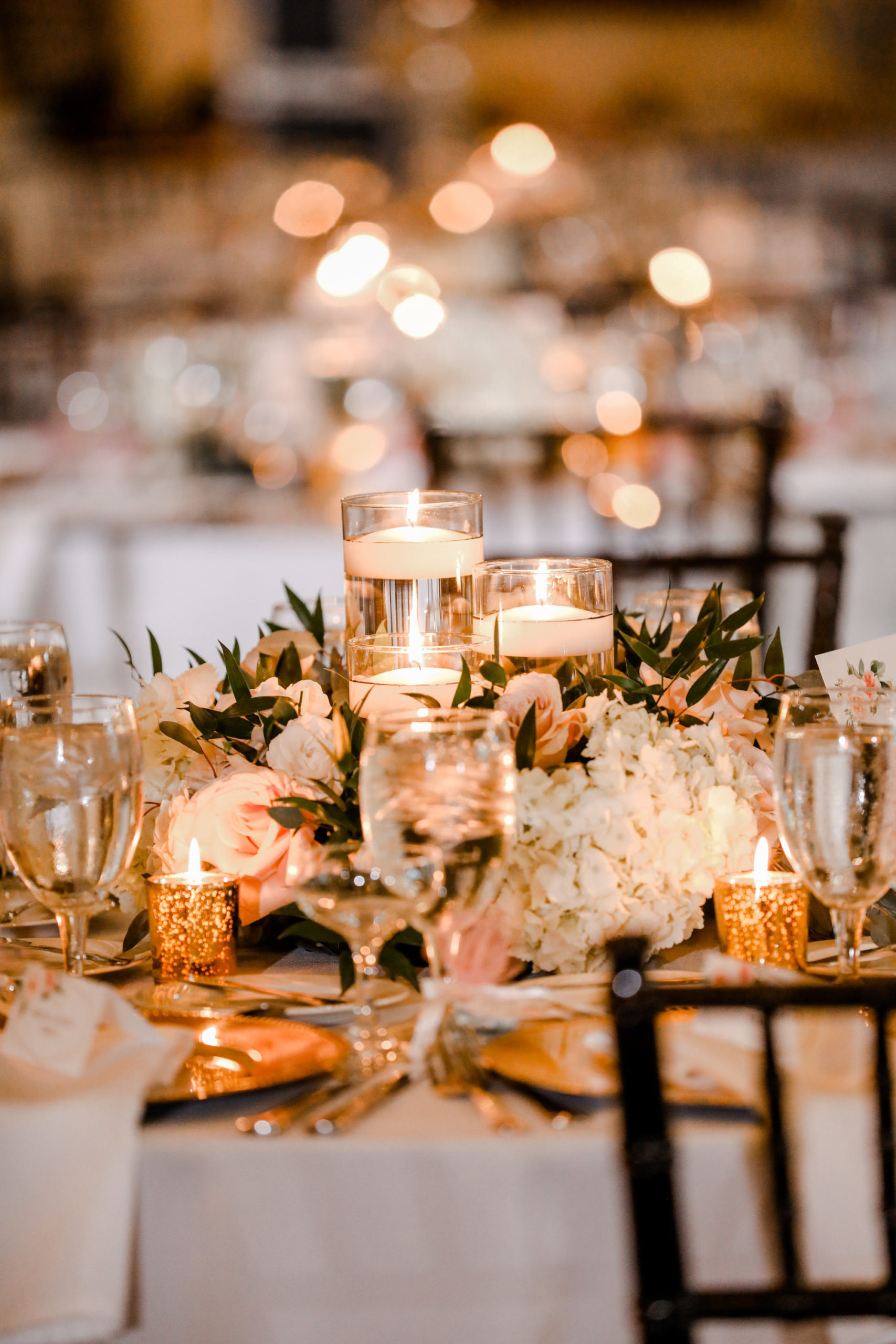 Tampa Wedding Venue Avila Golf & Country Club | Indoor Ballroom Reception with Chiavari Chairs and Chandeliers | White and Blush Dusty Rose | Low Floating Candle Centerpiece with Hydrangea Roses and Greenery