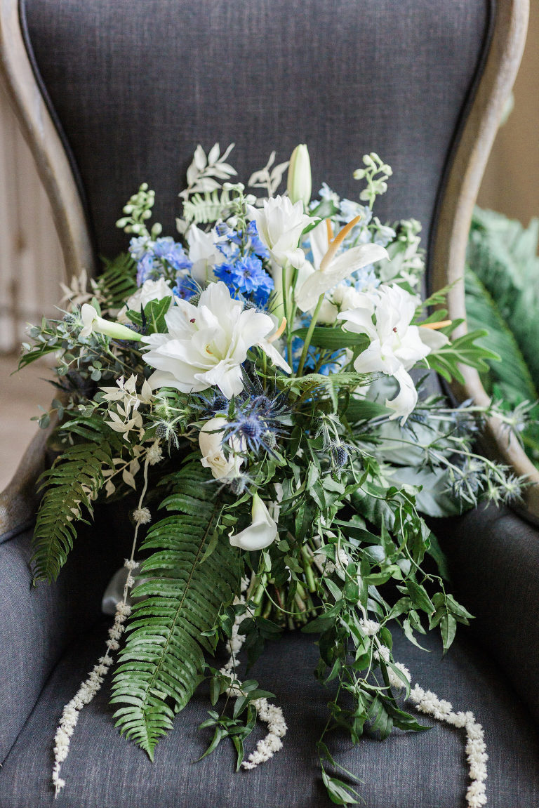 Bride Tropical Wedding Cascading Bouquet with Loose Greenery and Organic White Lilies and Blue Thistle