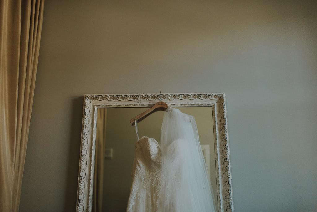 Martina Liana Lace Sweetheart Wedding Dress Shot | Bridal Gown and Veil Hanging Up Photo