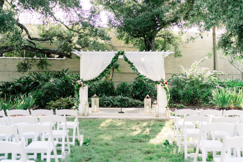 The Tampa Garden Club Tampa Wedding Venue | Garden Wedding Ceremony with Draped Arbor and Greenery Backdrop and White Garden Chairs