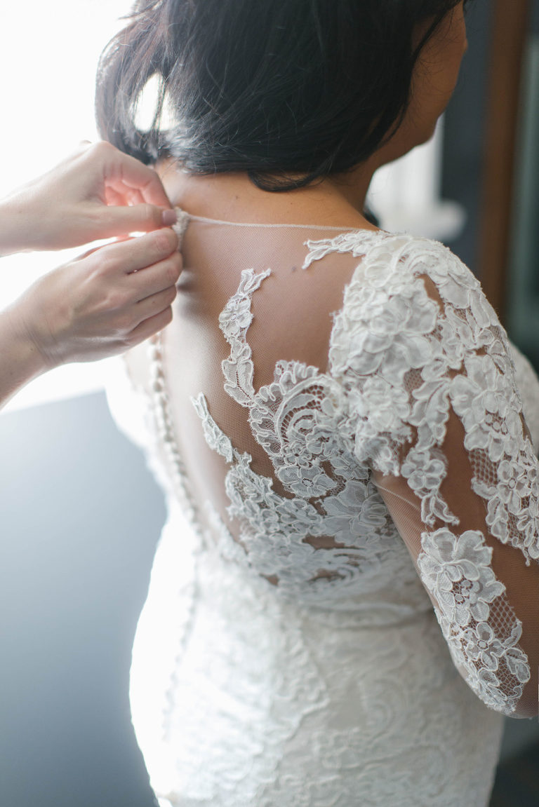Tampa Bay Bride Jessica from Parties A'la Carte Getting Ready Wedding Portrait Putting on Lace and Illusion Long Sleeve Fitted Wedding Dress