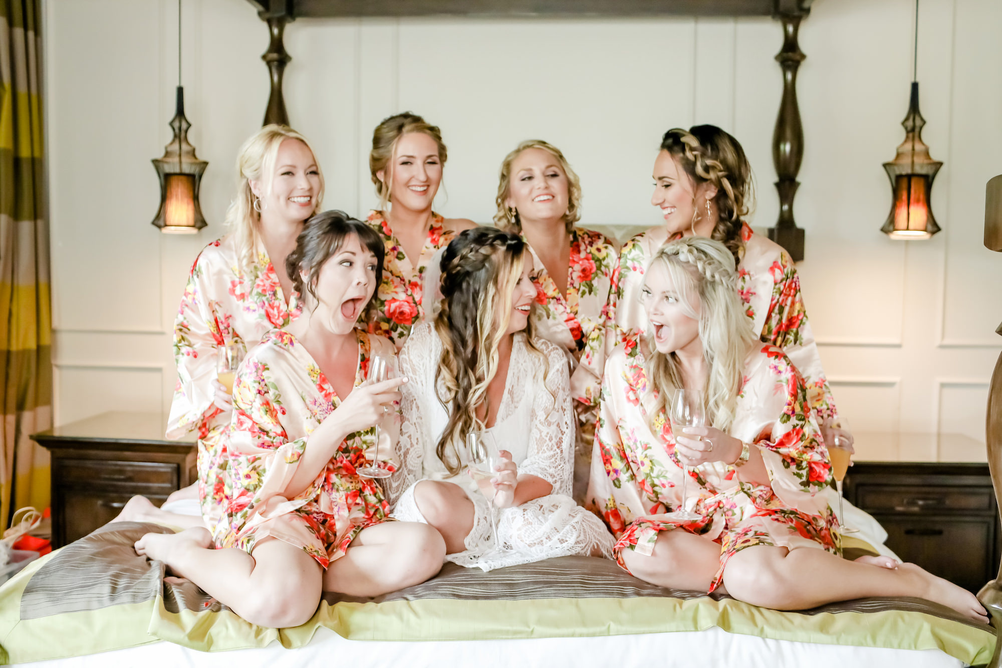 Tampa Bay Bride and Bridesmaid Getting Ready in Silk Floral Robes with Gold, Pink, Red, Yellow and Green, Wearing Braids and Drinking Champagne     Downtown St. Pete Wedding Hair and Make Up Artists Michele Renee The Studio   Tampa Bay Wedding Photographer Lifelong Photography Studio