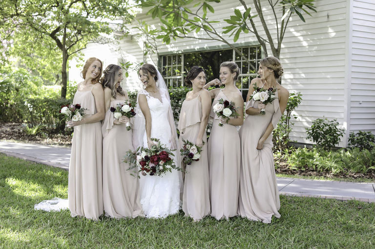 Bride in Lace Wedding Dress with Bridesmaids in Neutral Nude Dresses Holding Burgundy, Blush Pink and Ivory Roses with Greenery Floral Bouquet | Wedding Photographer Lifelong Photography Studio | Tampa Bay Wedding Planner Blue Skies Weddings and Events | Dress Shop Bella Bridesmaids