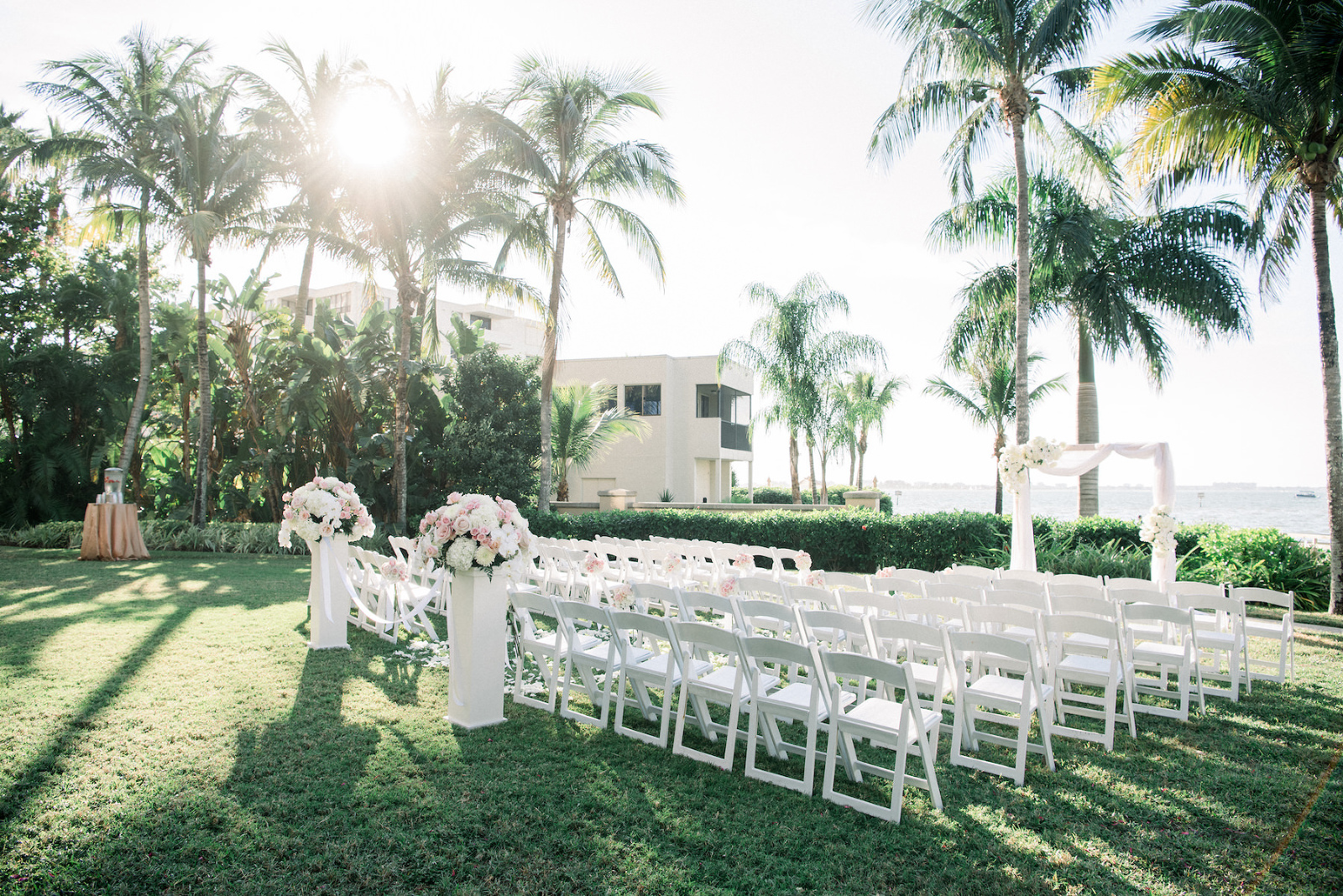 Classic Elegant Waterfront Garden Wedding Ceremony Decor, White Folding Chairs, Pedestals with Floral Arrangements, Rectangular Arch with Draping | Hotel Wedding Venue Ritz Carlton Sarasota | Tampa Wedding Planner Special Moments Event Planning