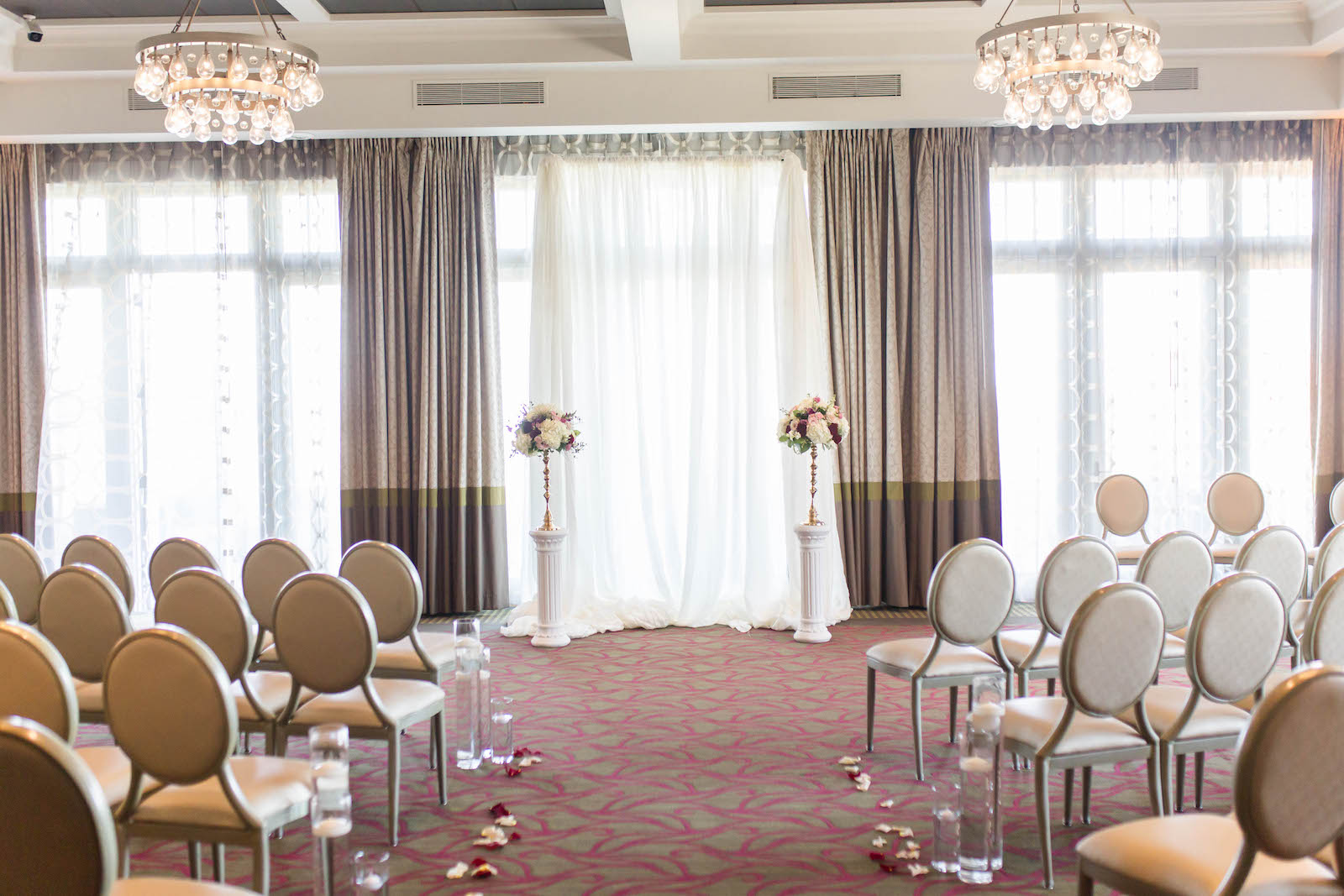 St. Pete Wedding Venue The Birchwood   Indoor Ballroom Wedding Ceremony with Floral Candlestick and Pipe and Drape Backdrop and Floating Candles down the Aisle