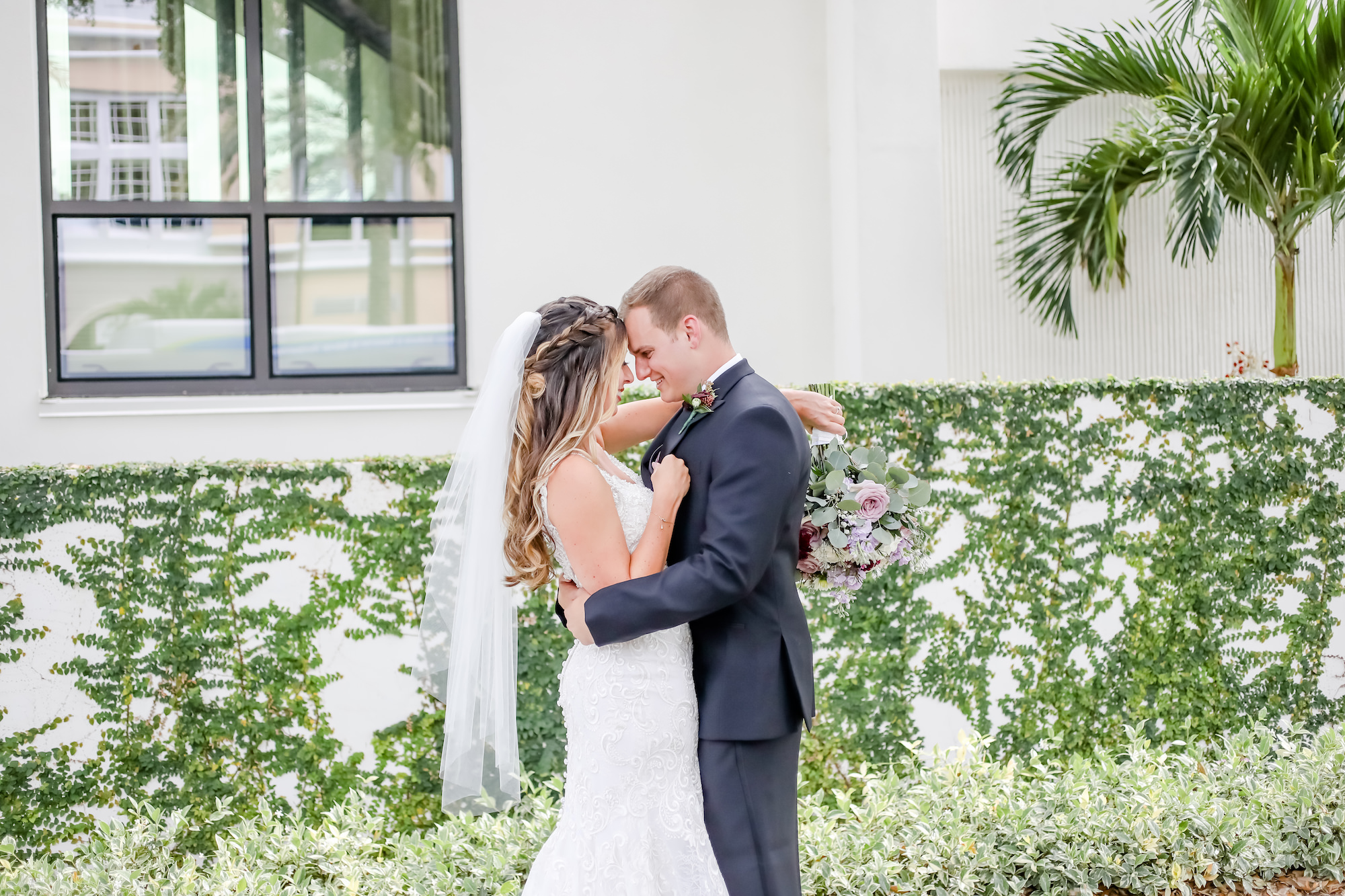 Downtown St. Pete Bride and Groom First Look Portrait, Bride Holding Mauve and Purple Floral Bouquet with Greenery   Florida Wedding Wedding Photographer Lifelong Photography Studio   Tampa Bay Wedding Venue The Birchwood