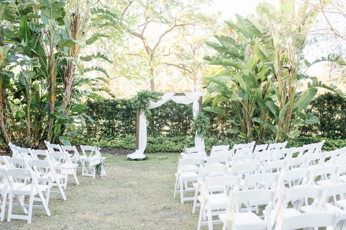 Tampa Wedding Venue the Tampa Garden Club   Outdoor Garden Wedding Ceremony with White Garden Chairs and Wood Arch with White Draping and Greenery Floral Arrangements