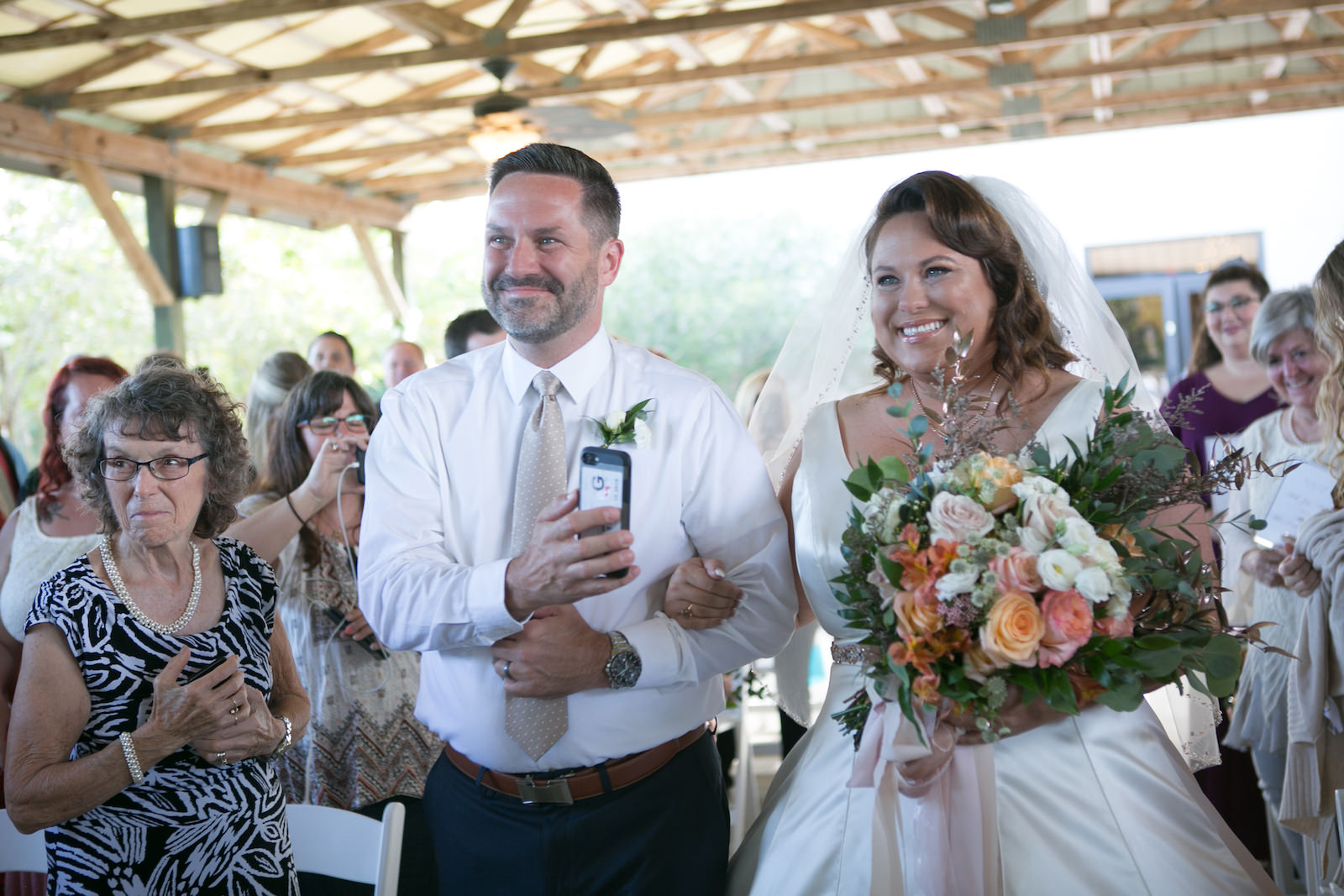 Tampa Bride Walking Down the Aisle Holding Colorful Spring Pink, White and Orange Roses with Greenery Floral Bouquet | Wedding Photographer Carrie Wildes Photography | Wedding Dress Truly Forever Bridal | Wedding Hair and Makeup Michele Renee the Studio