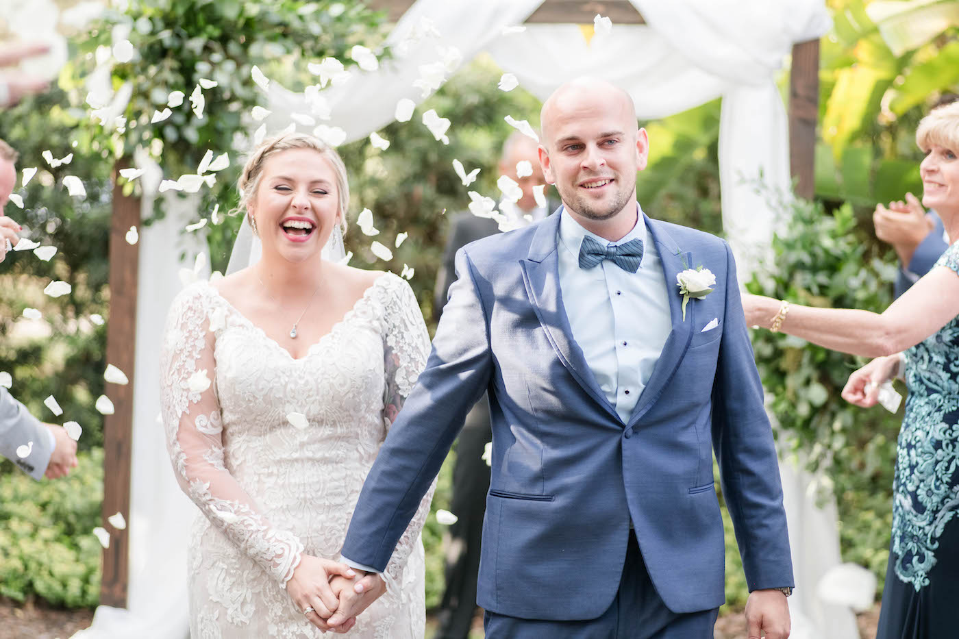 Bride and Groom Walking Down the Aisle in Rose Petal Toss   Ivory Lace Long Sleeve V Neck Bridal Gown and Groom in Blue Suit with Bow Tie