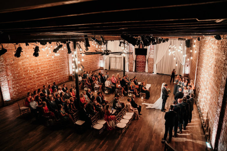 Florida Bride and Groom Exchange Vows During Wedding Ceremony, Interior Summer Ceremony with Exposed Red Brick Wall, Hardwood Floors and String Lighting | Historic Tampa Bay Wedding Venue NOVA 535 in Downtown St. Petersburg