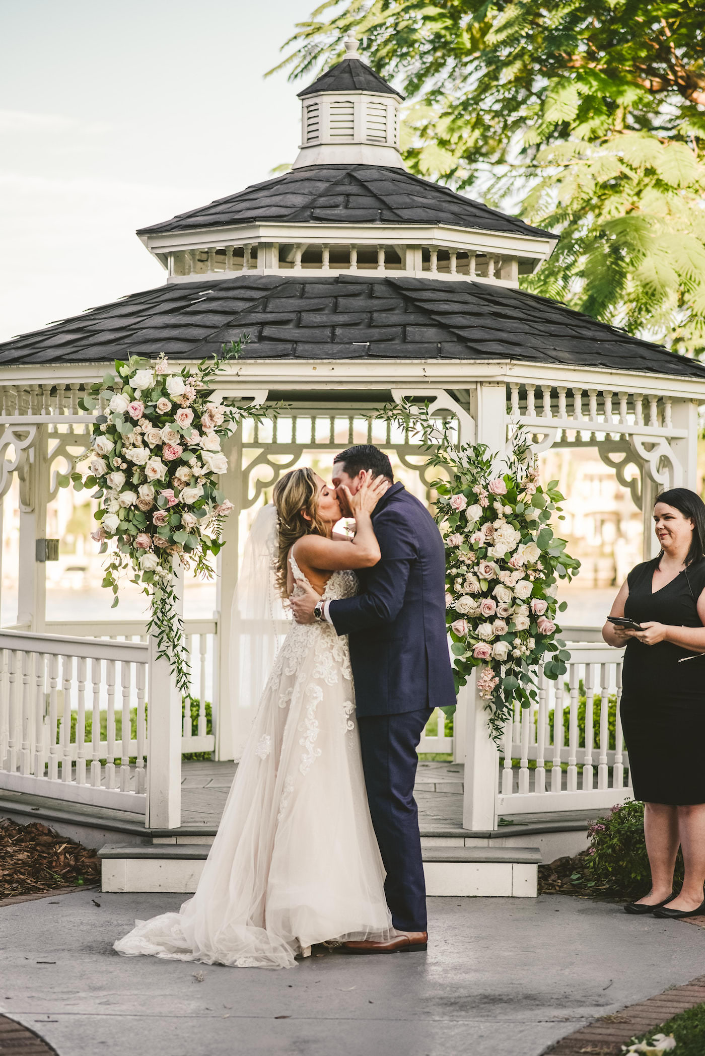 Bride and Groom First Kiss at Tampa Waterfront Garden Venue with Gazebo Backdrop and White and Blush Pink Rose and Greenery Floral Arrangements