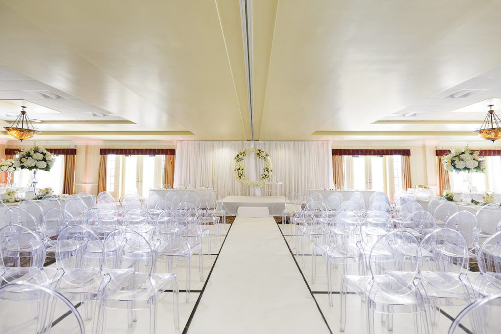 Romantic Classic Wedding Ceremony Decor, Ghost Acrylic Chairs, White Draping Backdrop with Round Ivory Floral Wreath | Tampa Bay Wedding Planner Special Moments Event Planning | Wedding Rentals Gabro Event Services | Clearwater Beach Wedding Venue Duvall Ballroom