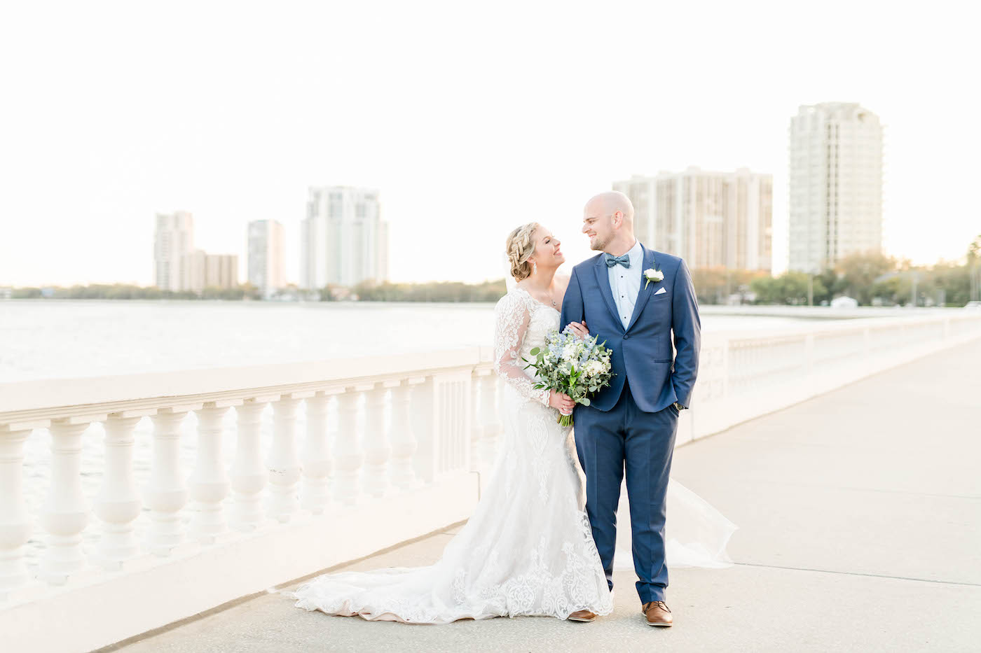 Bride and Groom Outdoor Portraits on Bayshore Boulevard Tampa   Ivory Lace Long Sleeve V Neck Bridal Gown and Groom in Blue Suit with Bow Tie   Blue and White Bridal Bouquet